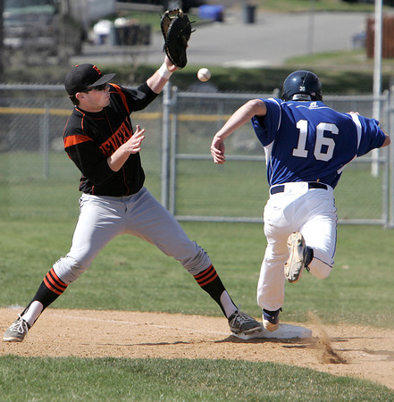 KEN YUSZKUS/Staff photo. Danvers' Richie Martino gets on 1st as Beverly's Sean Munzing wrestles with the ball during the Beverly at Danvers baseball game at Twi-Field.      4/25/14