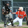 Danvers American catcher Brett Palladino, left, looks to make a play after forcing out Beverly pitcher Shane Cassidy (16) at the plate on Tuesday evening at Harry Ball Field in Beverly. DAVID LE/Staff photo. 7/8/14.