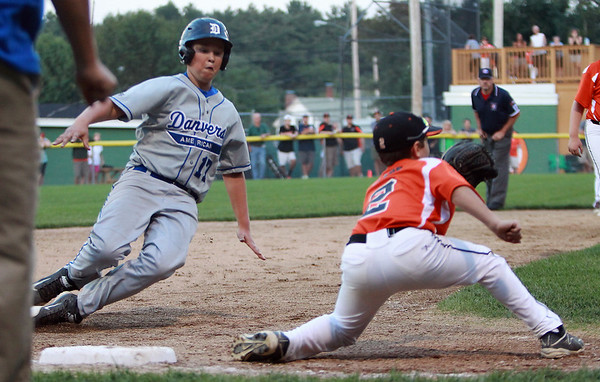 Danvers American first baseman JT Cashman (17) slides into third base as Beverly shortstop Brayden Clark waits for the throw on Tuesday evening at Harry Ball Field in Beverly. DAVID LE/Staff photo. 7/8/14.