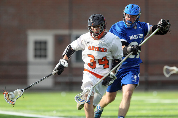 Beverly sophomore midfielder Jordan Rawding (34) protects the ball from Danvers defense Anthony Serino (20) while carrying it up the sideline during the third quarter of play. The Panthers advanced past the Falcons 11-10 on a last second goal by senior attack Matt Page. DAVID LE/Staff photo. 5/30/14.