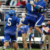Danvers senior Matty Flynn (1) leaps in the air and celebrates midfielder Jay Calcagno's second quarter goal as Stephen Goutzos (5) rushes over to join in. The Panthers advanced past the Falcons 11-10 on a last second goal by senior attack Matt Page. DAVID LE/Staff photo. 5/30/14.