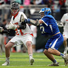 Beverly senior attack Matt Page (27) tries to drive to the net against Danvers midfielder Zach Persson (17) during the third quarter of play on Friday evening. The Panthers advanced past the Falcons 11-10 on a last second goal by senior attack Matt Page. DAVID LE/Staff photo. 5/30/14.