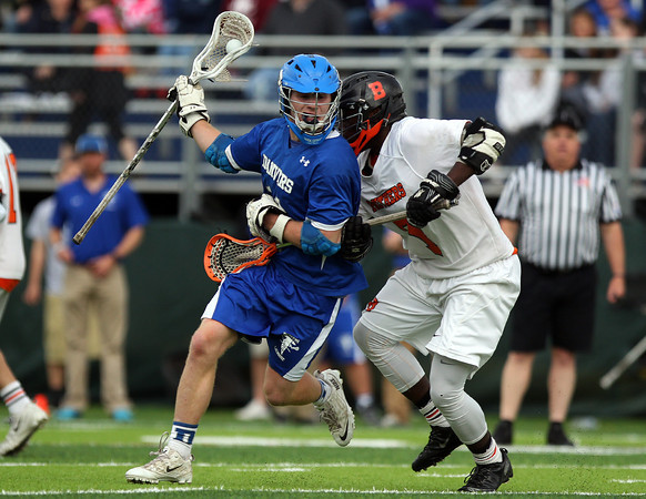 Danvers midfielder Jay Calcagno (11) shields the ball while being pressured by Beverly sophomore midfielder Peter Mulumba (7) on Friday evening at Endicott College in Beverly. The Panthers advanced past the Falcons 11-10 on a last second goal by senior attack Matt Page. DAVID LE/Staff photo. 5/30/14.