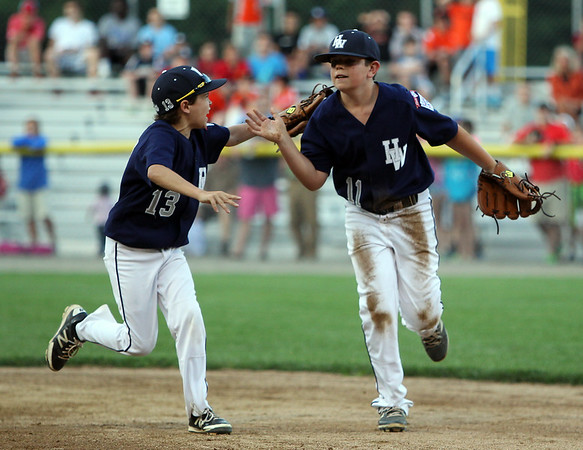 Hamilton-Wenham second baseman Conor Evers (13) enthusiastically greets shortstop Will Frain after he made a diving stop up the middle and flip to second base to retire a Beverly runner and leave the bases loaded on Thursday evening at Harry Ball Field in Beverly. DAVID LE/Staff photo. 7/10/14.