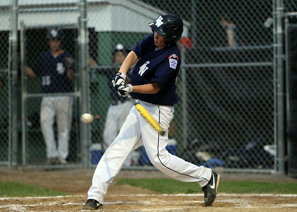 Hamilton-Wenham's Will Jones lines a single up the middle on Thursday evening at Harry Ball Field in Beverly. DAVID LE/Staff photo. 7/10/14.