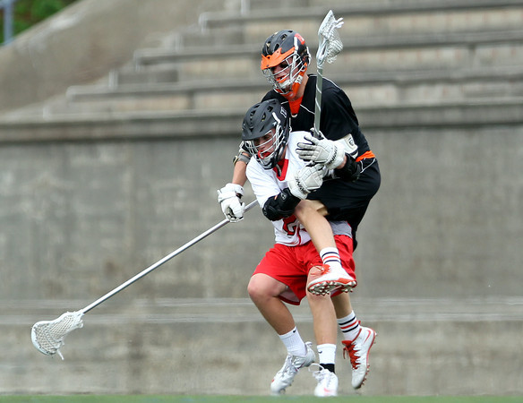 Beverly senior captain Ty Martz collides with Hingham junior Colin Filbotte while battling for a ground ball in the D2 State Semifinal at Harvard Stadium on Tuesday afternoon. DAVID LE/Staff photo. 6/10/14.