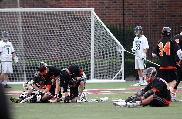 Beverly High School lacrosse players sit on the field at Harvard Stadium in shock and disbelief after they fell in overtime to Hingham 9-8 in the D2 State Semifinal on Tuesday afternoon. DAVID LE/Staff photo. 6/10/14.