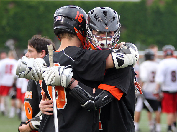 Beverly seniors Zach Duguid, left, and Matt Page, right, embrace after the Panthers overtime loss to Hingham in the D2 State semifinal on Tuesday afternoon at Harvard Stadium. DAVID LE/Staff photo. 6/10/14.
