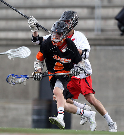 Beverly junior attack Nick Albano tries to evade a Hingham defender and drive to the net during the second quarter of play in the D2 State Semifinal at Harvard Stadium on Tuesday afternoon. DAVID LE/Staff photo. 6/10/14.