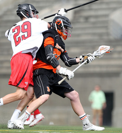 Beverly senior captain Matt Page dodges his way to the net to score a goal with Hingham senior Jackson Ullrich (29) draped all over him in the D2 State Semifinal at Harvard Stadium on Tuesday afternoon. DAVID LE/Staff photo. 6/10/14.