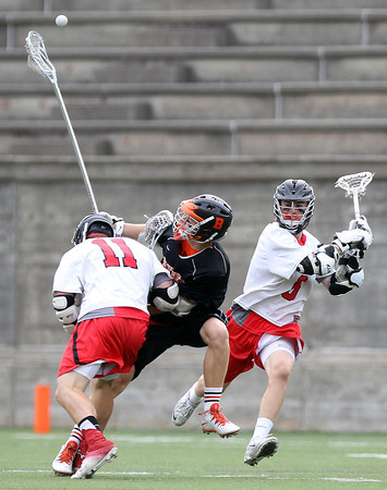 Beverly senior captain Ty Martz (3) loses control of the ball while being checked by Hingham sophomore Jacob Brodie (11) as senior Matt Rosso (5) closes in during the first quarter of play in the D2 State Semifinal at Harvard Stadium on Tuesday afternoon. DAVID LE/Staff photo. 6/10/14.
