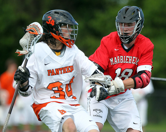 Beverly sophomore midfielder Jordan Rawding (34) tries to escape pressure from Marblehead freshman Manning Sears (18) during the first half of play. Behind four goals and five assists from junior attack Nick Albano the Panthers downed the Magicians 12-6 to capture the D2 North Title at Bertram Field in Salem on Saturday afternoon. DAVID LE/Staff photo. 6/7/14.