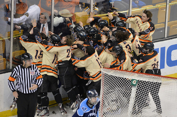 Beverly celebrates behind the glass behind their net, seconds after clinching the Division 2 state championship over Medfield at the TD Garden Sunday night in Boston. Staff photo by Desi Smith