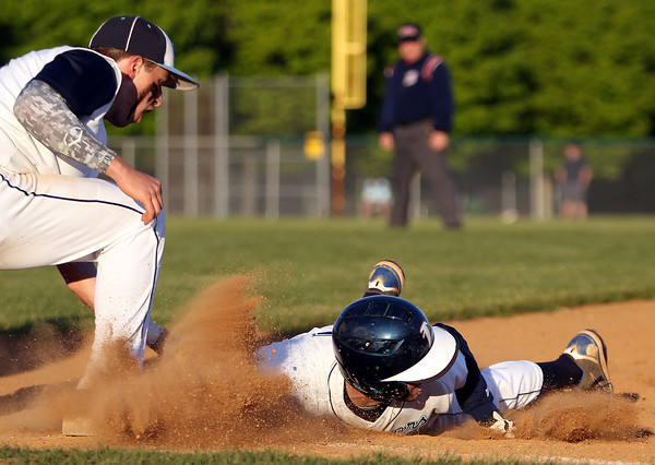 Danvers senior Ryan Kelleher kicks up a cloud of dirt as he dives headfirst back into the base before Dracut first baseman Zach Millanakos can apply the tag. DAVID LE/Staff photo. 6/1/14.