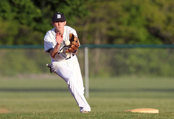 Danvers shortstop Andrew Olszak cleanly fields a high hopper and throws to first to retire a Dracut runner on Sunday evening. DAVID LE/Staff photo. 6/1/14.