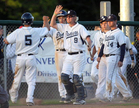 Danvers junior Cris Valles (5) gets greeted by his teammates after he scored to put the Falcons up 3-1 on a successful suicide squeeze by Devonn Allen. DAVID LE/Staff photo. 6/1/14.