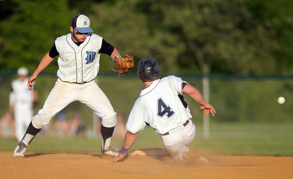 Danvers senior Tyler Dustin (4) slides safely into second base for a steal as the ball scoots away from Dracut second baseman Jack McKenna on Sunday evening.  DAVID LE/Staff photo. 6/1/14.
