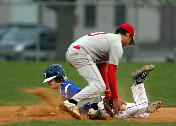 Danvers sophomore Danny Lynch slides safely into second base for a steal after Salem shortstop Zach Leblanc (3) can't handle the throw from catcher Austin Connolly. DAVID LE/Staff photo. 5/9/14.
