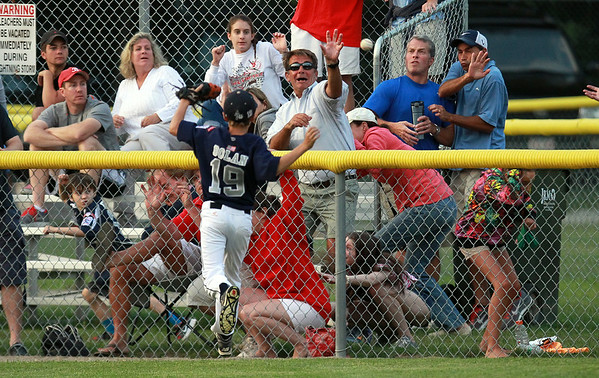 Fans in centerfield scatter as a line drive home run clears the fence as Hamilton-Wenham center fielder Lenny Dolan can only look on. The Generals lost to Barnstable 12-1 in a shortened 4 inning contest on Friday evening at Harry Ball Field in Beverly. DAVID LE/Staff photo. 7/25/14.