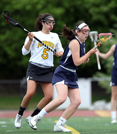 Hamilton-Wenham's Kayla Frain (17) keeps control of the ball while being pressured by Bishop Fenwick's Annette Ruggiero (5) during the first half of play. The Crusaders barely edged out the Generals 8-7 with two late goals by Merry Harrington in the first round of the MIAA D2 state tournament at Donaldson Field at Bishop Fenwick High School on Tuesday afternoon. DAVID LE/Staff photo. 5/27/14.