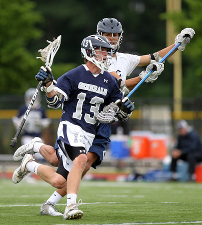 Hamilton-Wenham senior captain Matt Curran (13) drives hard to the net while being held off by Cohasset junior Pat Holway. The Generals fell to the Skippers 10-6 in the D3 State semifinal at Woburn High School on Wednesday evening. DAVID LE/Staff photo. 6/11/14