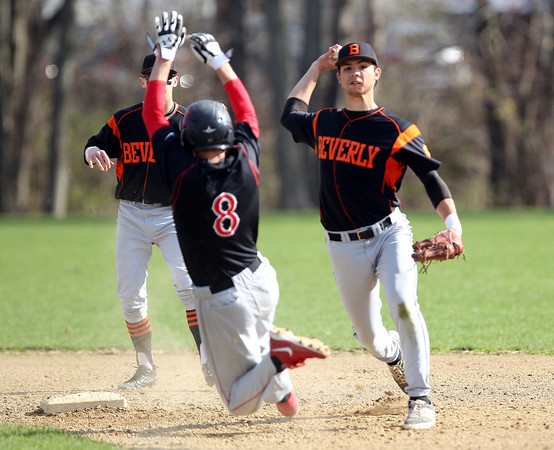 Beverly senior shortstop John Berchoff, right, steps around sliding Marblehead runner Kyle Maulden (8) and fires to first to complete a Panthers double play. DAVID LE/Staff photo. 5/2/14