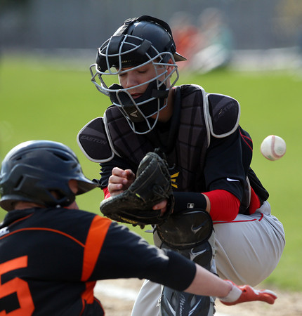 The baseball pops out of Marblehead catcher Harrison Engstrom's glove as he goes to tag Beverly's Nick Cotraro as he slides across home plate with the first run of the game. DAVID LE/Staff photo. 5/2/14