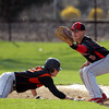 Marblehead senior first baseman Tom Koopman (5) waits for the throw as Beverly senior Kevin Cuneo (10) slides headfirst back to the base on a pickoff attempt. DAVID LE/Staff photo. 5/2/14