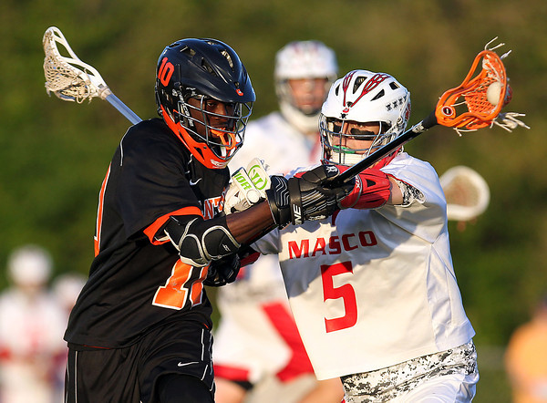 Masco senior attack Max Craig tries to dislodge the ball from Beverly junior defense Serge Jolicoeur (10) during the second quarter of play in the North Shore Cup on Wednesday evening. DAVID LE/Staff photo. 5/21/14.