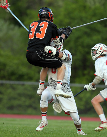 Beverly junior Bryan Flaherty (33) gets checked while airborne by Masco junior defense Corey Tines as the two battled for a loose ball. DAVID LE/Staff photo. 5/21/14.