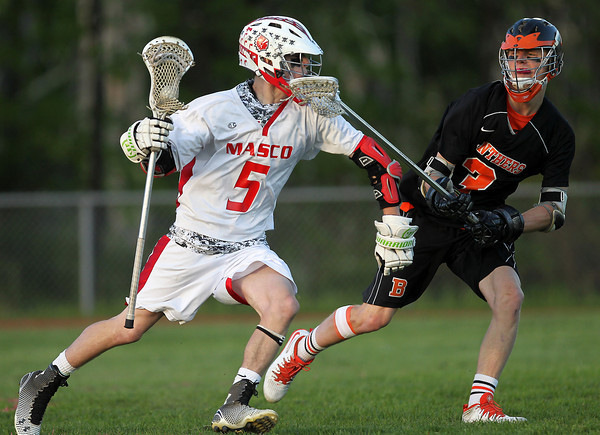Masco senior attack Max Craig (5) tries to ward off Beverly senior defense Ty Martz (3) as he carries the ball in the offensive zone on Wednesday evening. DAVID LE/Staff photo. 5/21/14.