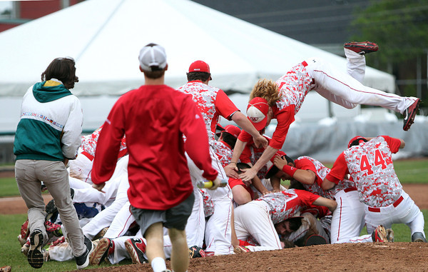 The Masco baseball team pig piles on the pitchers mound after the final out of the D2 State Championship, a 10-2 Chieftains win over Westwood at Campanelli Stadium in Brockton on Thursday afternoon. DAVID LE/Staff photo. 6/12/14