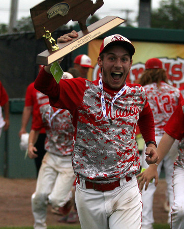 Masconomet senior Tom Budrewicz runs with the D2 State Championship trophy after his team won the title with a 10-2 win over Westwood at Campanelli Stadium in Brockton on Thursday afternoon. DAVID LE/Staff photo. 6/12/14