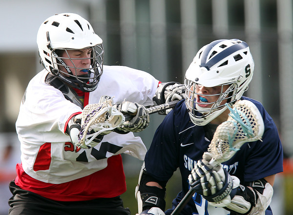 Swampscott's Jason Dignan (25) tries to spin away from a check from Salem midfielder Eamon Williamson (16) during the second half of play on Thursday afternoon. DAVID LE/Staff photo. 5/8/14