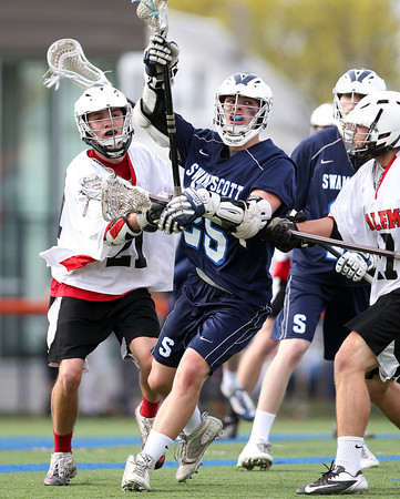 Swampscott's Jason Dignan (25) tries to escape pressure from Salem midfielder Craig Denehy (21) during the third quarter of play on Thursday afternoon. DAVID LE/Staff photo. 5/8/14