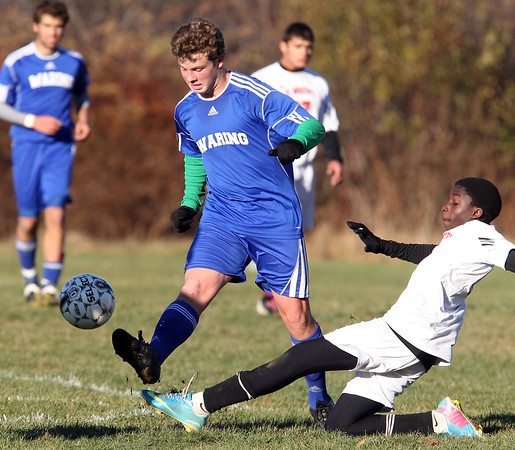 Beverly: Waring School midfielder Nat Lyman, left, boots the ball upfield while avoiding a sliding St. Andrew's player during the first half of play on Wednesday afternoon. David Le/Salem News