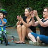 Two-year-old Everett Dugal, of Salem, applauds riders along Washington Square East, with his mom Anna Dugal, and Ginny Moulton, during the Witches Cup around Salem Common on Wednesday evening. DAVID LE/Staff photo. 8/6/14.