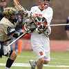 Beverly: Beverly senior midfielder Brendan Flaherty fends off a cross-check from a Malden Catholic player as he drives to the net on Saturday afternoon. David Le/Salem News