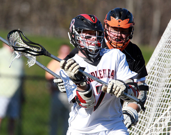 Marblehead: Marblehead attack Trevor Jones controls the ball behind the Beverly net while being pursued by Beverly defenseman Mike Dooling during the first quarter of play.  David Le/Salem News