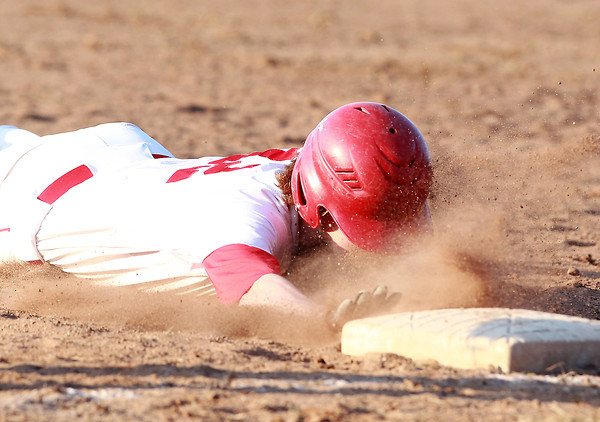 Topsfield: Masco's Greg Dougherty gets a face-full of dirt as he slides safely back into first base after an RBI single against Beverly on Friday evening. David Le/Salem News