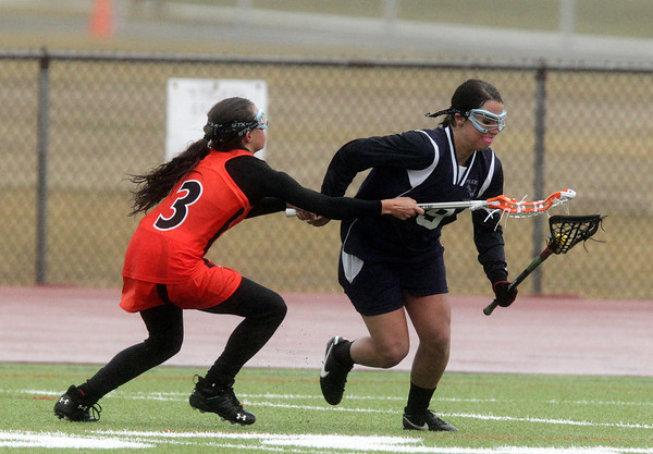 Beverly: Peabody's Victoria Digiacomo protects the ball while being stick-checked by Beverly's Alicia Cecchini, left, on Friday afternoon. David Le/Salem News
