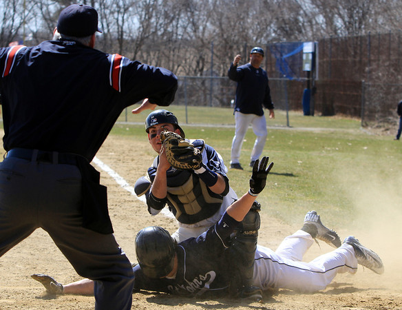 Peabody: Peabody High School catcher Brandon Polignone holds up the ball for the home plate umpire to see as St. John's Prep senior Alex Moore throws his arms out trying to get a safe call. David Le/Salem News