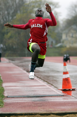 Beverly: Salem junior long jumper Aaron Palmer soars in the air and extends himself forward during his second attempt on a cold, rainy Tuesday afternoon. David Le/Salem News