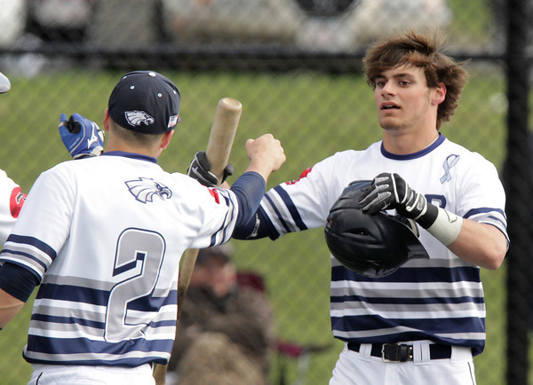 Danvers: St. John's Prep senior Alex Moore gets a fist bump from teammate Tommy Buonopane after scoring the go-ahead run in the bottom of the third inning against Malden Catholic on Monday afternoon. David Le/Salem News