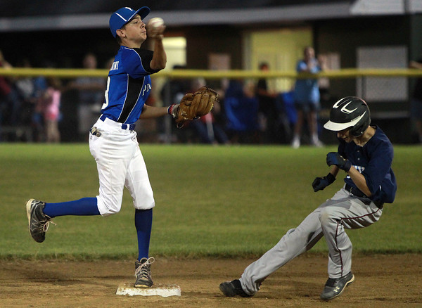Beverly: Peabody second baseman Josh Cerratani, left, fires the ball around a ducking Danvers baserunner to first, but is just late to turn the double play. David Le/Salem News
