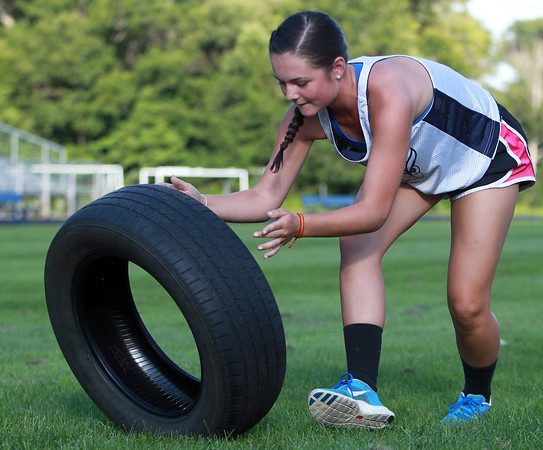 Hamilton: Hamilton-Wenham sophomore Molly Eagar flips over a tire during one of the events of the first Iron Woman Competition at Hamilton-Wenham High School on Thursday afternoon. David Le/Salem News