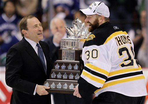 Boston Bruins goalie Tim Thomas (30) is presented the Conn Smythe Trophy as the most valuable player of the postseason by NHL commissioner Gary Bettman after the Boston Bruins beat the Vancouver Canucks 4-0 in Game 7 of the NHL hockey Stanley Cup Finals to win the championsship, Wednesday, June 15, 2011, in Vancouver, British Columbia. (AP Photo/Julie Jacobson)