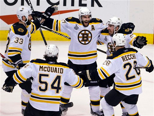 Boston Bruins center Patrice Bergeron, center, celebrates with teammates after scoring against the Vancouver Canucks during the first period of Game 7 of the NHL hockey Stanley Cup Finals on Wednesday, June 15, 2011, in Vancouver, British Columbia. (AP Photo/The Canadian Press, Jonathan Hayward)