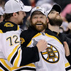 Boston Bruins goalie Tim Thomas (30) is congratulated by teammates as he is announced as the winner of the Conn Smythe Trophy as the most valuable player of the postseason, after the Bruins defeated the Vancouver Canucks 4-0 in Game 7 of the NHL hockey Stanley Cup Finals to in the Stanley Cup, Wednesday, June 15, 2011, in Vancouver, British Columbia. (AP Photo/Julie Jacobson)