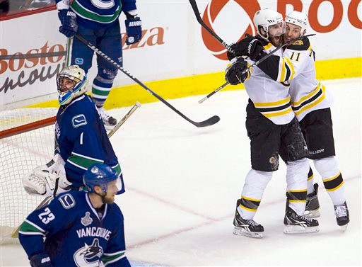 Boston Bruins center Patrice Bergeron celebrates with Bcenter Gregory Campbell, right, after scoring on Vancouver Canucks goalie Roberto Luongo (1) as Canucks defenseman Alexander Edler (23) skates nearby during the second period of Game 7 of the NHL hockey Stanley Cup Finals on Wednesday, June 15, 2011, in Vancouver, British Columbia. (AP Photo/The Canadian Press, Jonathan Hayward)